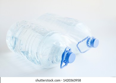 Natural Spring Water in five liter bottles on the white surface with own with nylon packing.