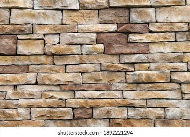 natural stack rock stone wall building facade with deep shadows in natural sunlight