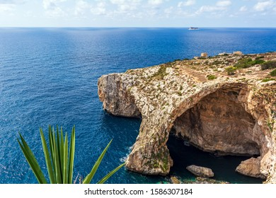 Natural stone arch of Blue Grotto and sea caverns in Malta, with agave plant in foreground and small Hamrija Watchtower in the background. Blue Grotto seascape.