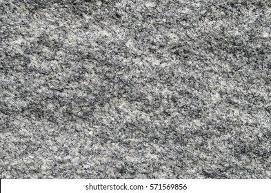 Natural stone grey granite background. Bright hard grey granite rock texture. Grey granite stone background. Grey granite untreated surface. Facing material full frame horizontal texture.