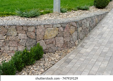 Natural stone with a metal mesh near the lawn in the landscape design