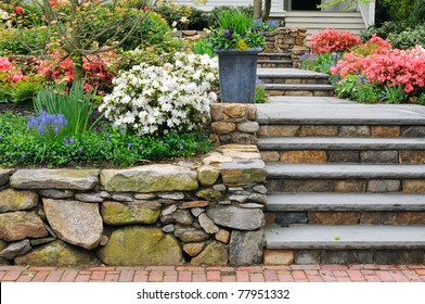 Natural stone steps and retaining wall, planter and garden border framing home entrance. Beautiful hardscape, colorful landscape design