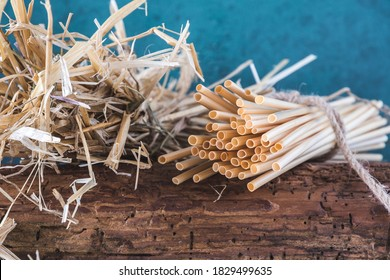 Natural straw drinking straws and a bundle of straw on an old wooden beam, blue background. Concept of sustainability, no plastic.
