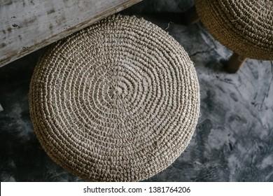 Natural straw round pouf cushion chair with wooden legs, grey concrete floor. Close up details. Minimalist loft coffee shop, restaurant, home interior design