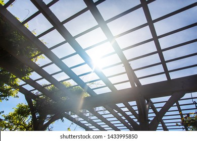 Natural sunlight showing through wooden arbor canopy roof