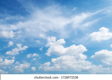 Natural sunny blue sky background with beautiful puffy white cumulus clouds & fluffy cirrus cloudscape on bright daylight horizon in tropical summer sunlight & exotic sun ray at sunny & sunshine day
