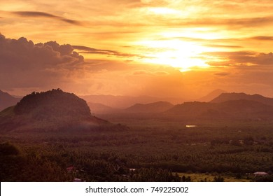 Natural Sunset Over Field Or Meadow. Bright Dramatic Sky And Dark Ground. Countryside Landscape Under Scenic Epic Sky At Sunset Dawn Sunrise. Sun Over Skyline, Horizon. Warm Colors.
