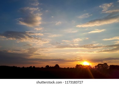 Natural Sunset Sunrise Over Field Or Meadow. Bright Dramatic Sky And Dark Ground. Countryside Landscape Under Scenic Colorful Sky At Sunset Dawn Sunrise. Sun Over Skyline