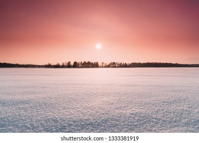 Natural Sunset Sunrise Over Field Or Meadow. Pink Color Sky Over Winter Snowy Ground. Landscape Under Scenic Sky At Sunset Dawn Sunrise. Skyline, Horizon.