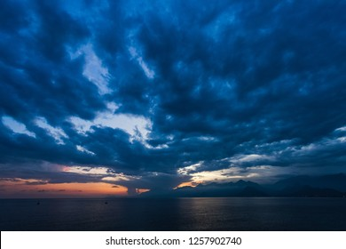 Natural sunset or sunrise time over calm sea water and mountains. Charming dramatic cloudy dark sky background. Night is coming. Horizontal color photography.