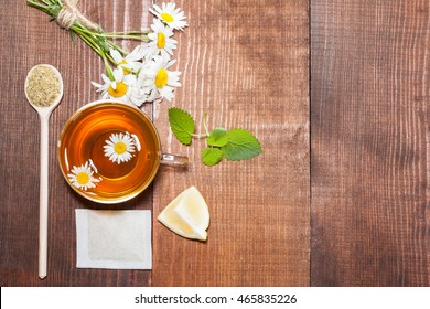 Natural tea set for quick recovery; composition of chamomile tea, bunch of chamomile flowers, lemon and melissa - copyspace
