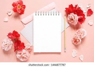 Natural template with blank notepad and various vintage roses on the pink background, top view
