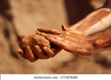 Natural terracotta clay piece held in hands. Wet clay material for sculpture or modeling
