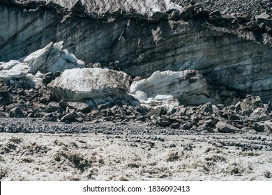 Natural texture of big glacial wall with crevasses close-up. Atmospheric nature background with ice boulders near icy broken wall with cracks. Big peace of ice and stones near surface of glacier.
