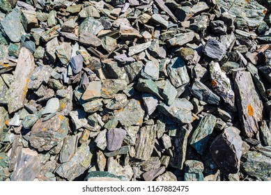 Natural texture of mountain of friable boulders close up. Detailed background of gray stones with orange moss. Mountainside with copy space.
