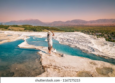 Natural travertine pools and terraces in Pamukkale. Cotton castle in southwestern Turkey, girl in white dress with hat