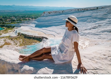 Natural travertine pools and terraces in Pamukkale. Cotton castle in southwestern Turkey, girl in white dress with hat natural pool Pamukkale