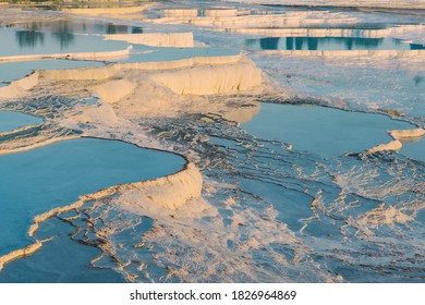 Natural travertine pools and terraces at sunset in Pamukkale, Turkey