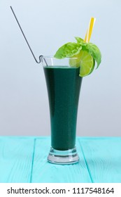 Natural vegetable cocktail with kiwi and other greens. A cocktail is decorated with lime, basil and yellow straw. A fresh drink for people who watch their health.