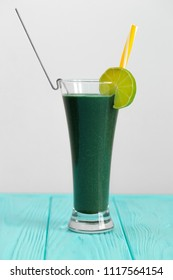 Natural vegetable cocktail with kiwi and other greens. A cocktail is decorated with kiwi with a yellow straw. A fresh drink for people who watch their health.