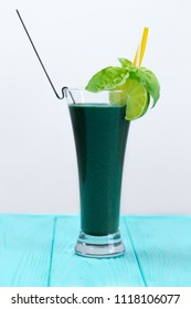 Natural vegetable cocktail on the white background with kiwi and other greens. A cocktail is decorated with lime, basil and yellow straw. A fresh drink for people who watch their health.