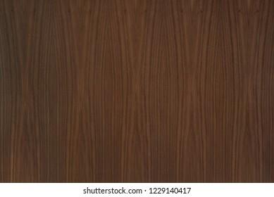 Natural veneered walnut MDF board varnished with matt varnish textured background.