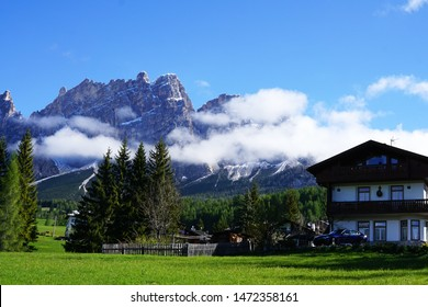 Natural village among snowy and rocky mountain at Dolomiti (Dolomites) range with cloudy blue sky -Cortina d'Ampezzo located in Veneto,Italy