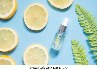Natural vitamin c serum, skincare, essential oil products. Cosmetic glass vial with fresh juicy lemon fruit slice and herbal on light blue background. Beauty product branding mock-up. Top view.