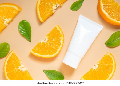 Natural vitamin c skincare products w/ fresh juicy orange fruit slice and green leaf on orange background. Cosmetic beauty product branding mock-up for moisturizing cream, lotion, foam or shampoo.