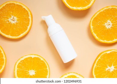 Natural vitamin c skincare products w/ fresh juicy orange fruit slice on orange background. Cosmetic beauty product branding mock-up for moisturizing cream, lotion, serum or essential oil. Top view.