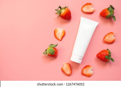 Natural vitamin c skincare tube w/ fresh strawberries fruit on pink background. Cosmetic beauty product branding mock-up for brightening cream, body lotion, facial foam or shampoo. Copy space.