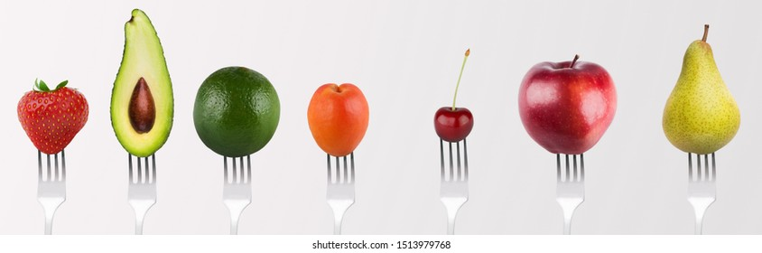 Natural Vitamins. Collage of separately fruits and vegetables on forks on grey background, panorama
