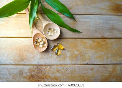 Natural vitamins and supplements in wooden spoons on wood table with leaf blackground.