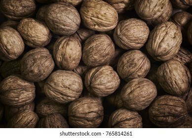 Natural walnut background pattern texture Abstract walnuts heap pattern background Blurred edges frame Natural food in-shell nuts walnuts pattern backdrop Walnuts in shell background dramatic contrast