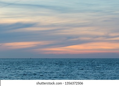Natural washed pastel cloudscape. Sea and wispy cloud sky at dawn. Soft background image. Painterly watercolor backdrop unaltered landscape sunrise. Simple beautiful ocean horizon.