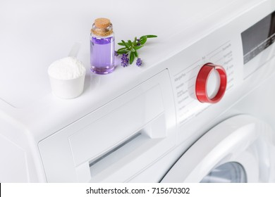 natural washing powder with essential oil and lavender flowers over washing machine