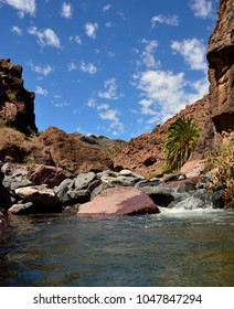 Natural water coming down the ravine, blue sky and clouds, Tirajana, Gran canaria