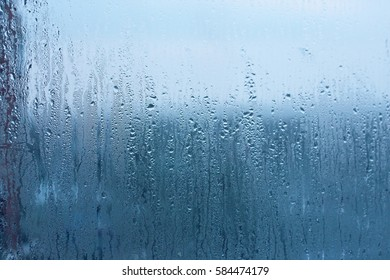 Natural water drop background. Window glass with condensation high humidity, large droplets flow down, cold tone. Collecting and streaming down