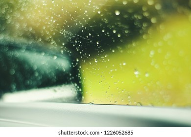 Natural water drops on window glass with green background