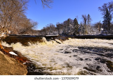 The natural waterfall at Kletzsch Park in Glendale Wisconsin along the Milwaukee River with snow covered trees in the distance.