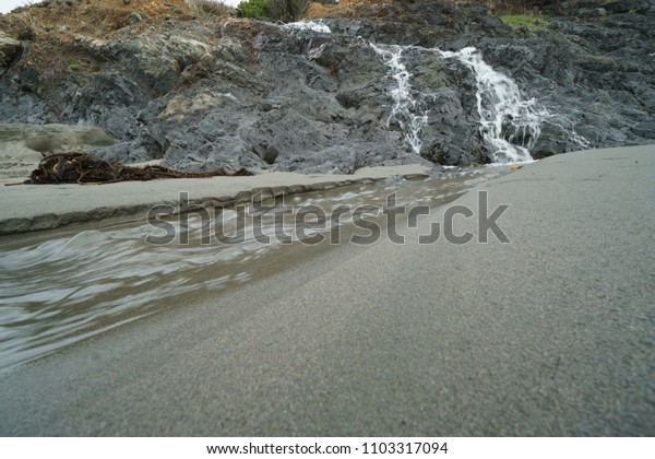 Natural waterfall over cliffs to sand beach.