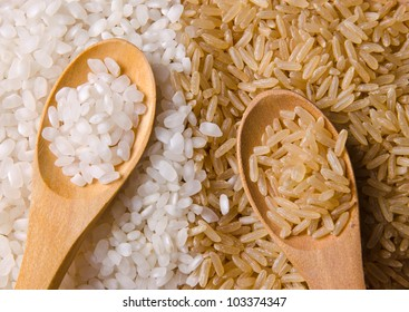 Natural white and brown long rice in wood spoons.