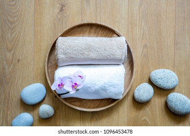 natural and white towels and ayurveda pebbles on round wooden tray and background for concept of fresh femininity, clean pampering and luxury sensuality, above view still life