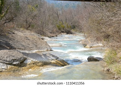 A natural and wild river in Provence, flows through waterfalls under a bridge, between stones embankments, hedges and trees .