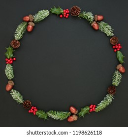 Natural winter and Christmas abstract wreath with snow covered fir, holly, ivy, mistletoe, acorns and pine cones on dark grey background. Traditional christmas greeting card for the festive season.