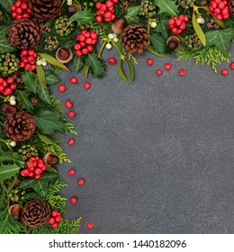 Natural winter and Christmas background border with holly and loose berries, mistletoe, ivy, cedar leaves and pine cones on grunge grey background with copy space.