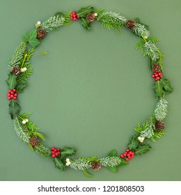 Natural winter and Christmas wreath with cedar cypress and snow covered fir leaf sprigs, holly berries, ivy and mistletoe on mottled green background. Traditional christmas card for the festive season