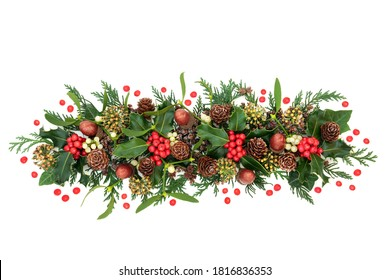 Natural winter floral decoration with holly, loose red berries, ivy, mistletoe, cedar cypress leaves, pine cones & acorns on white background. Traditional nature theme for Christmas & New Year.