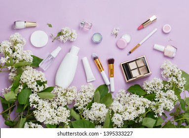 Natural woman make up cosmetics with spring white lilac bloom. Top view. Spring female decorative cosmetics on purple background. Natural organic cosmetic for make up. Cosmetic and brushes in blossom