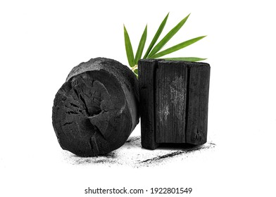 Natural wood charcoal with bamboo leaves isolated on white background.